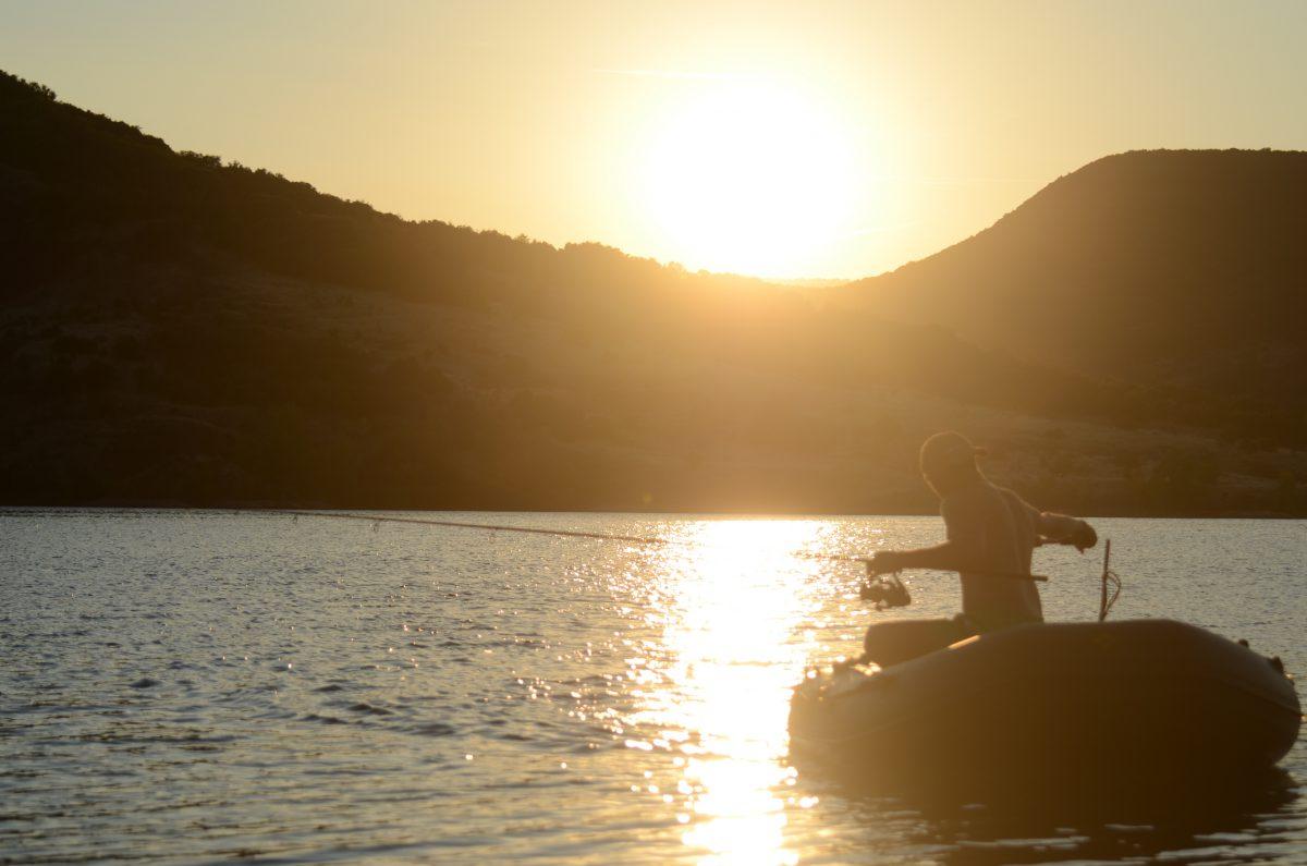 Sonnenuntergang am Salagou mit Karpfenangler der die Rute mit dem Boot auslegt